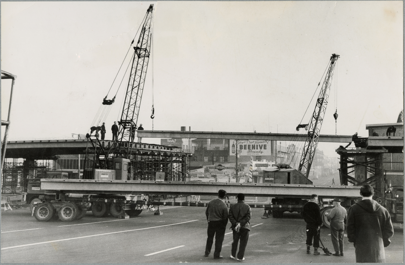Black and white photograph of workers watching cranes manoeuvre large concrete girder
