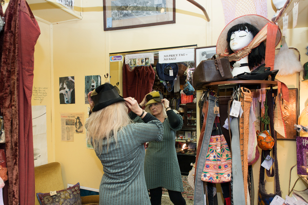 Shelley tries on a hat at her shop Ménage a Trois