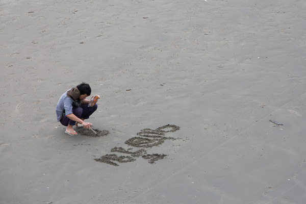 Man writing in sand on New Brighton beach
