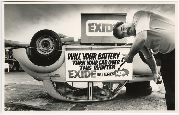 Exide car battery advertisement on an overturned car