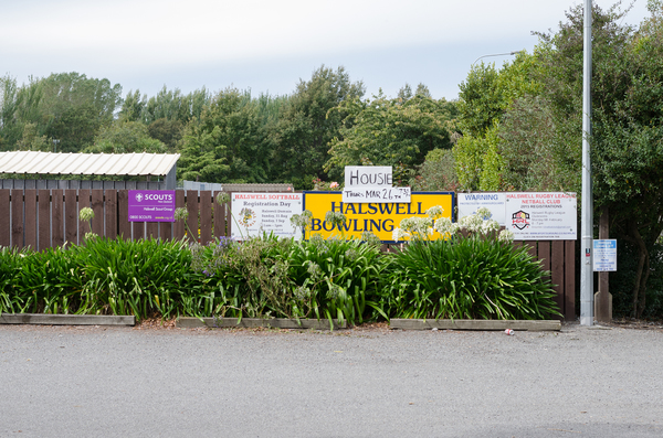 Signs on the outside west fence of the Bowls club