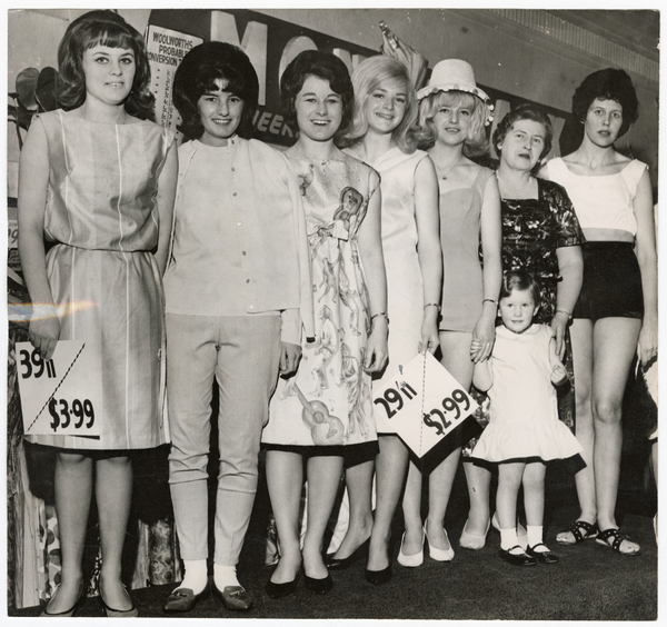 Models holding decimal price tags, Woolworths