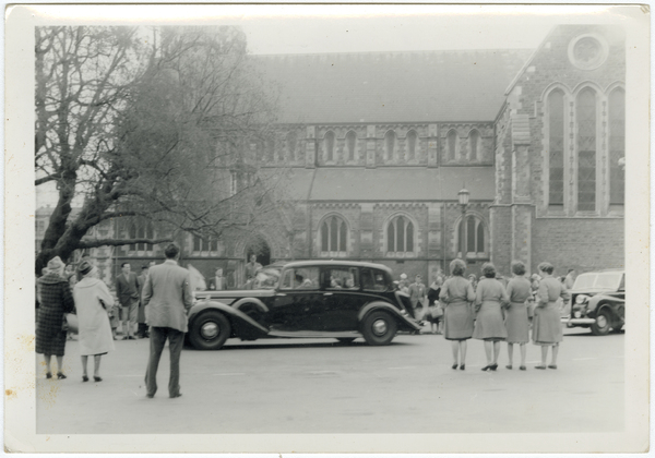 People watching a car outside the Cathedral