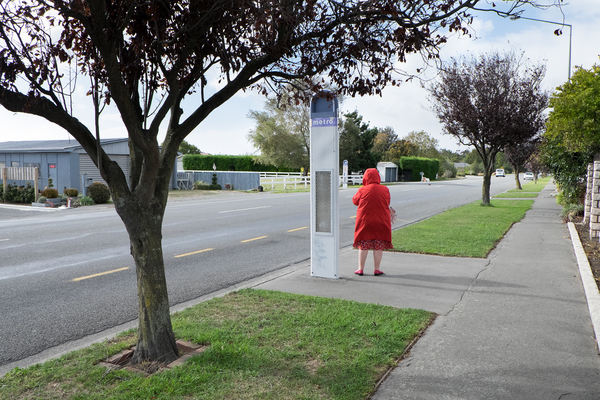 Woman waits at bus stop in Halswell