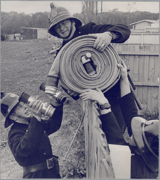 Firefighters moving hoses into a paddock