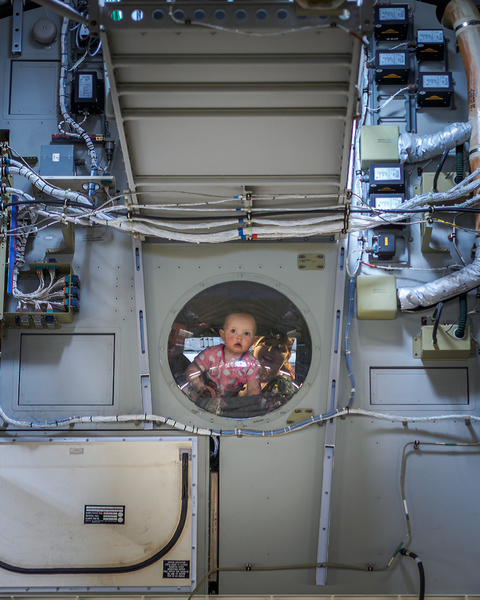 Infant looking over the cargo bay of a C-17 Globemaster III